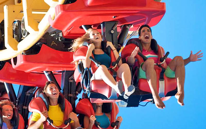 People sat in a red rollercoaster in the air and screaming
