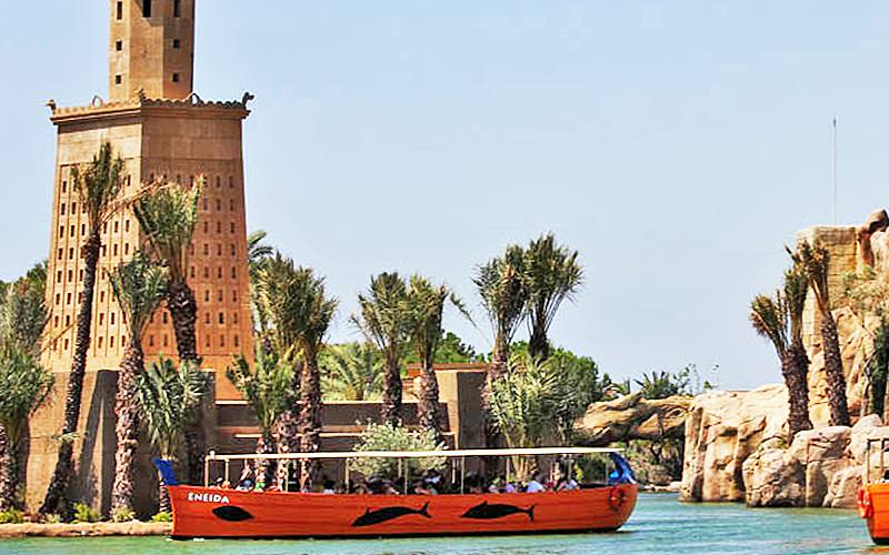 A boat on the water at Terra Mitica theme park with a building in the background