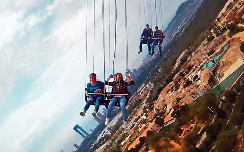 Four people sat in swings with Benidorm in the background