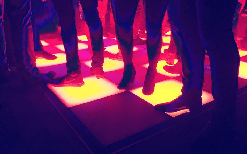 People dancing on a light-up dance floor