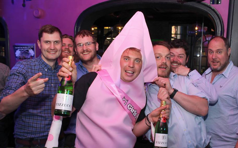 A group of men in a nightclub, one of them is dressed as a penis