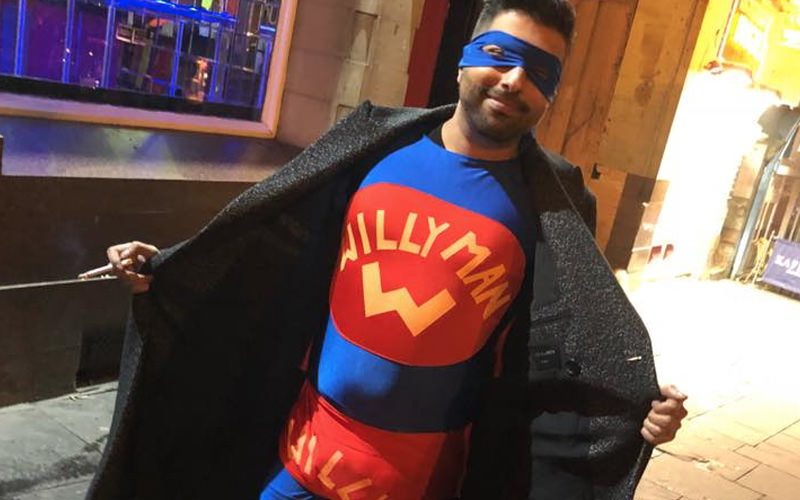 A man dressed in a superhero outfit, posing with his coat open