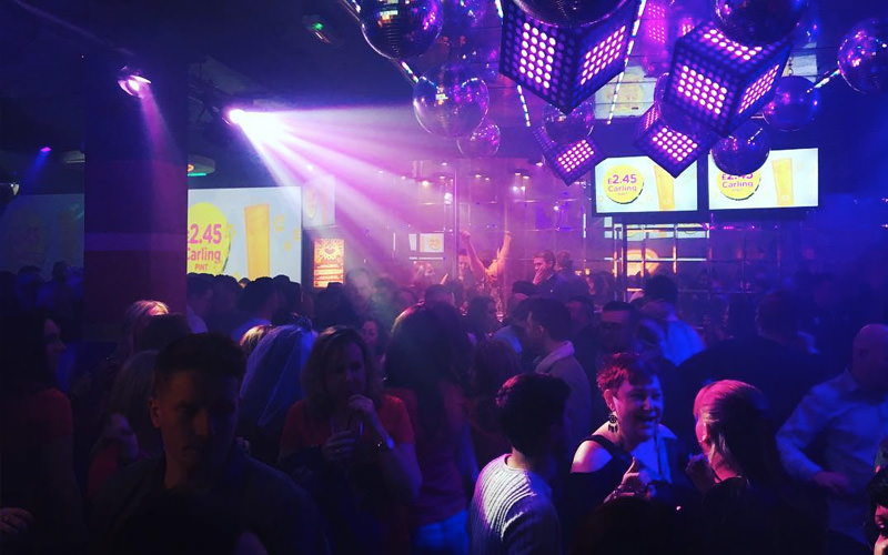 A large group of people dancing in a nightclub under purple strobe lights