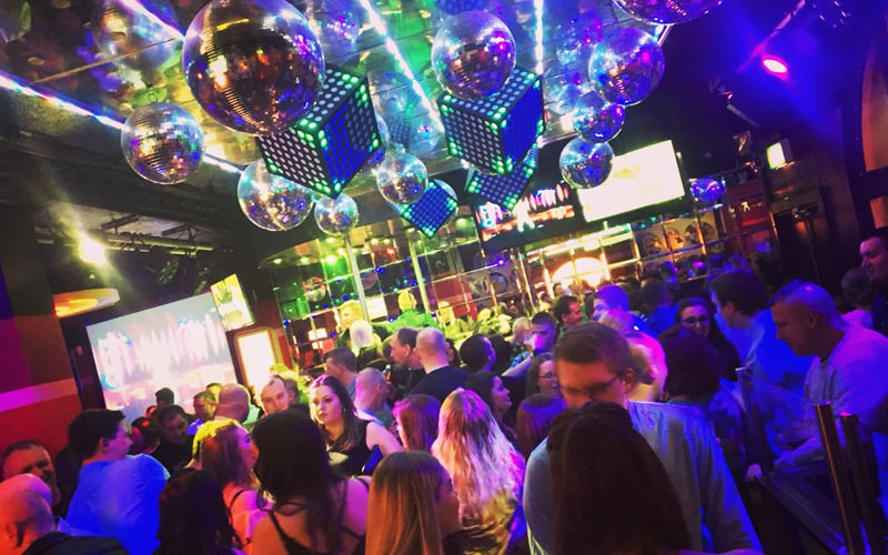 A large group of people in a nightclub with several disco balls above them and plenty of colourful lights