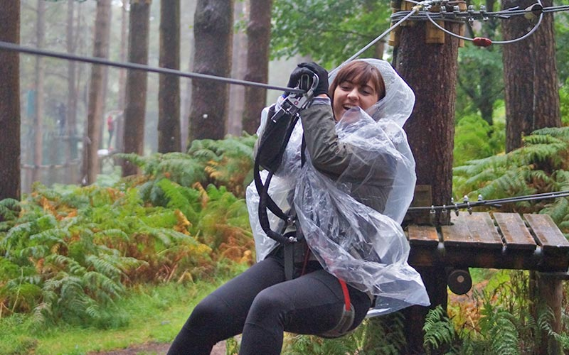 A girl zip-wiring between trees