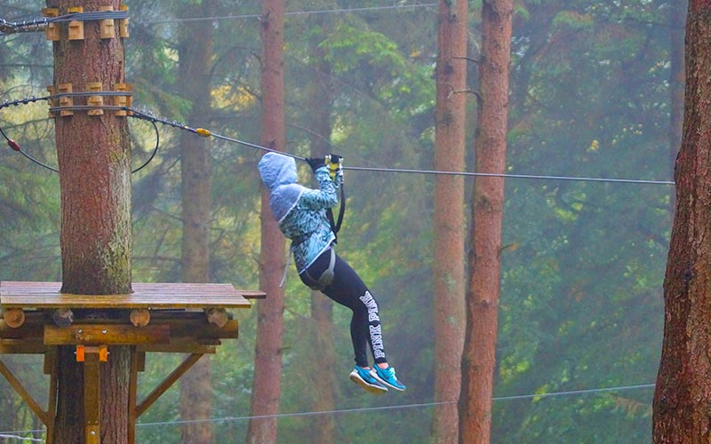 A girl using a zip-wire to swing between trees