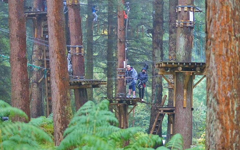 A woman being shown how to navigate a treetop assault course