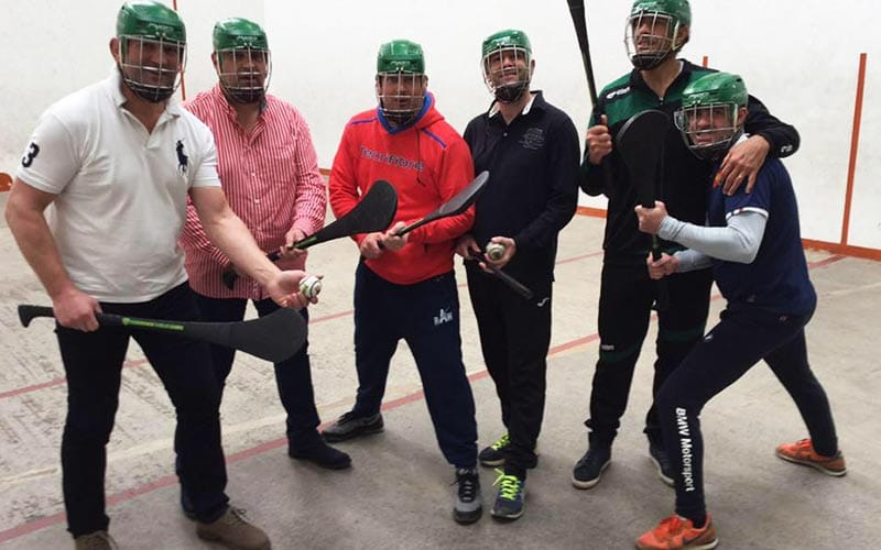 Some people holding sticks, with helmets on, preparing to play some Gaelic Games