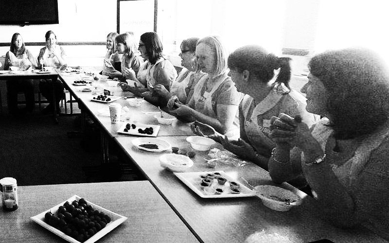 A black and white image of some women making chocolates