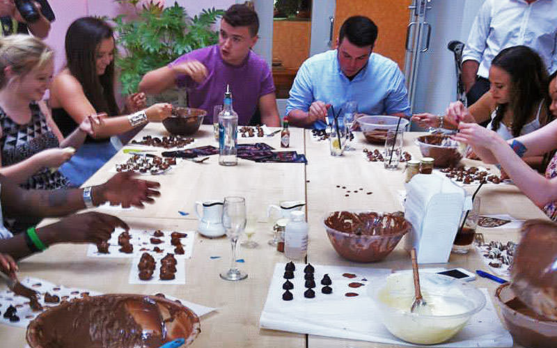 Men and women smiling, talking and making chocolates together