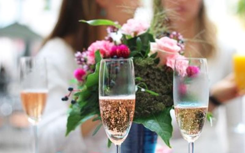 Three glasses of champagne with a bouquet of flowers in the back