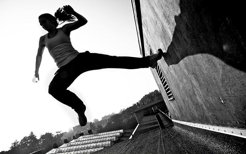 Black and white image of a woman jumping off a wall