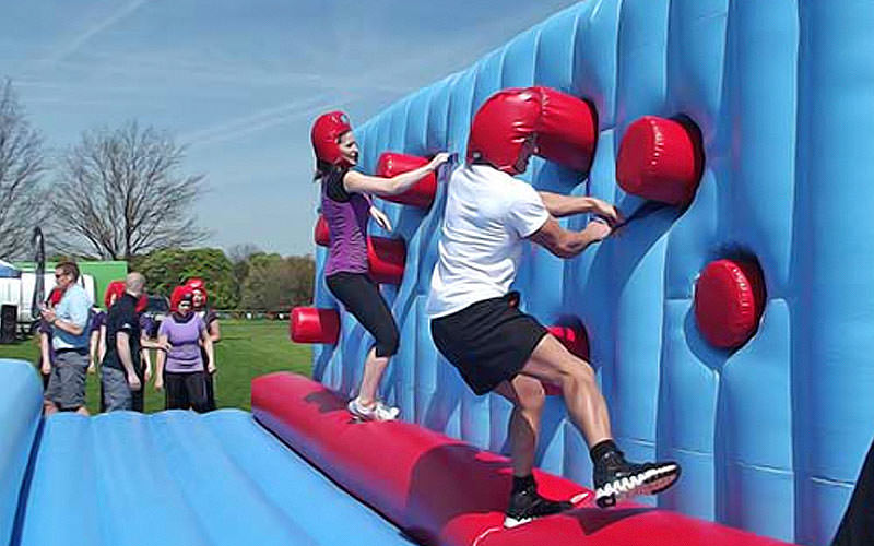Two people climbing an inflatable wall, with red fists popping out