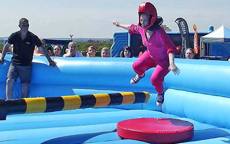 A woman jumping over a moving pole on an inflatable