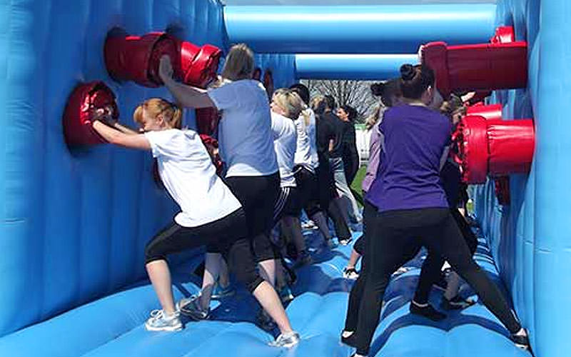 People in a blue inflatable, pushing against red tubes on the wall