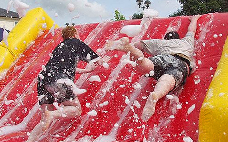 Two men attempting to climb a foamy inflatable