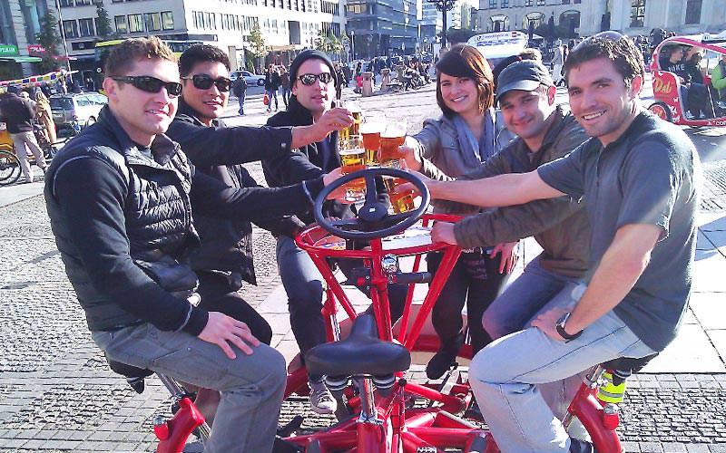 Group of people toasting with beer and sat on a conference bike