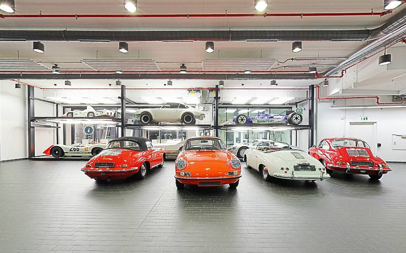 Four Porsches lined up in a garage, with different sporty versions on shelves in the background