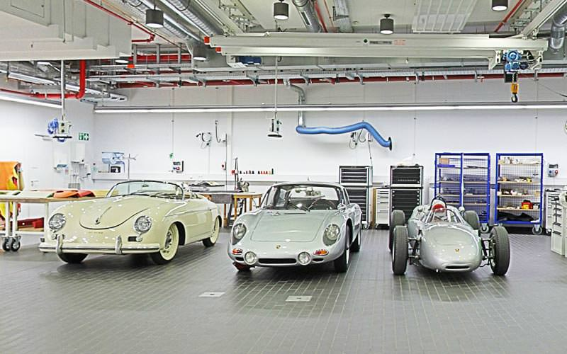 Three Porsche models in a warehouse type building