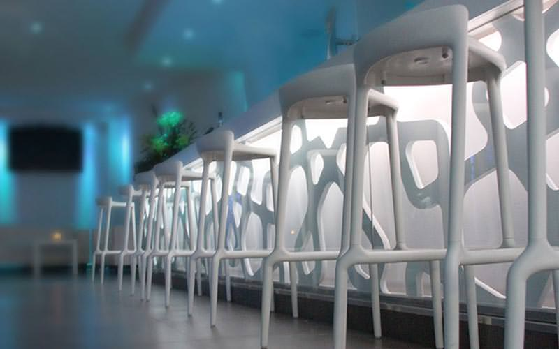 Some white bar stools lined up along the bar in Benidorm's Moon Club