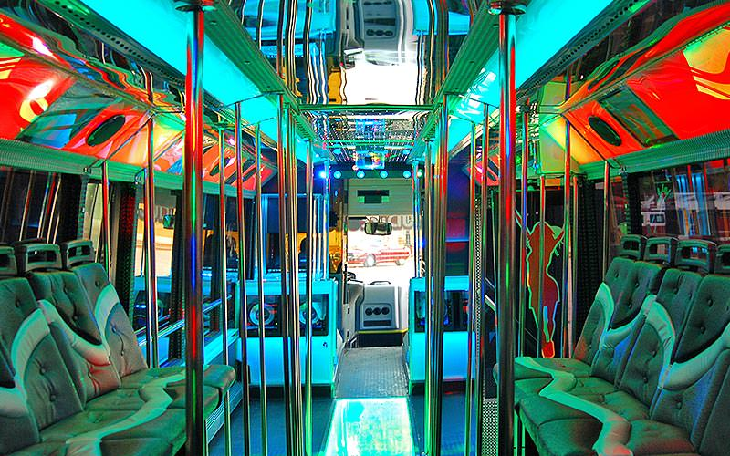 The interior of a party bus, with seating on the sides and poles in the middle