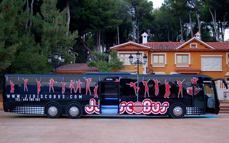 Exterior of black party bus with red illustrations of people dancing, during the day