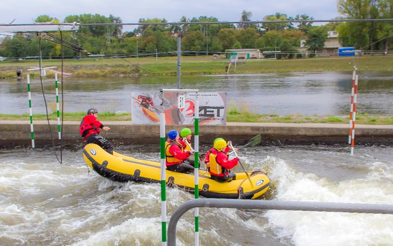 Four people paddling in a raft on an outdoor, white water rafting course