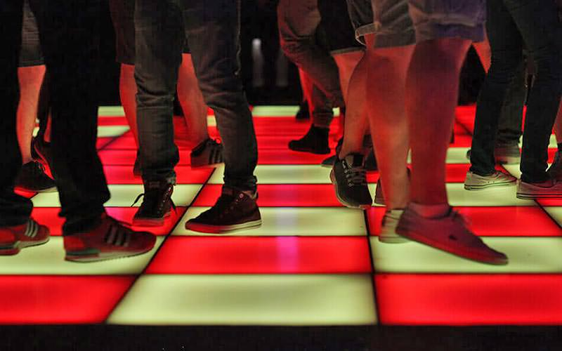 People's feet on a red and white lit-up dance floor