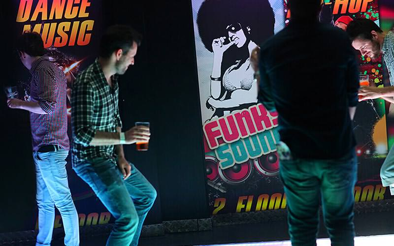 Four people dancing in a club, in front of dance posters on a wall