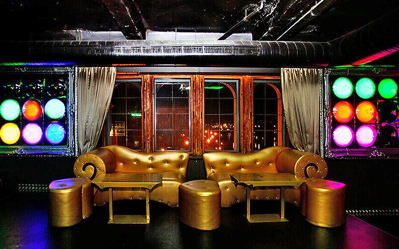 Gold couches and plush gold stools in a dark room, with different coloured lights on the wall, in a club