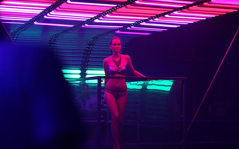 A woman in underwear, stood on a platform in a club