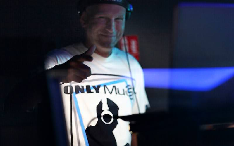A DJ, wearing headphones, sticking his phone up to the camera