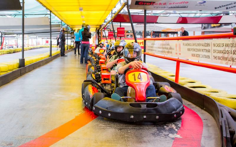 A line of people sat in go karts on an indoor track
