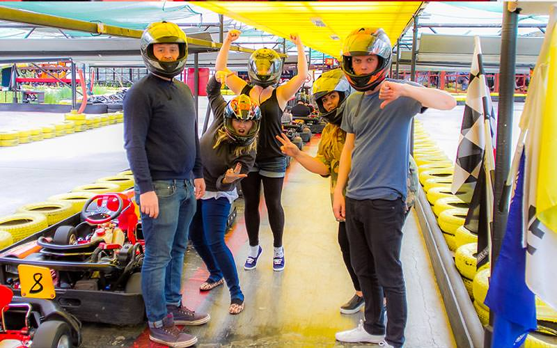 People posing for the picture in front of a line of go karts