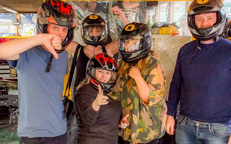 Five people posing with helmets on