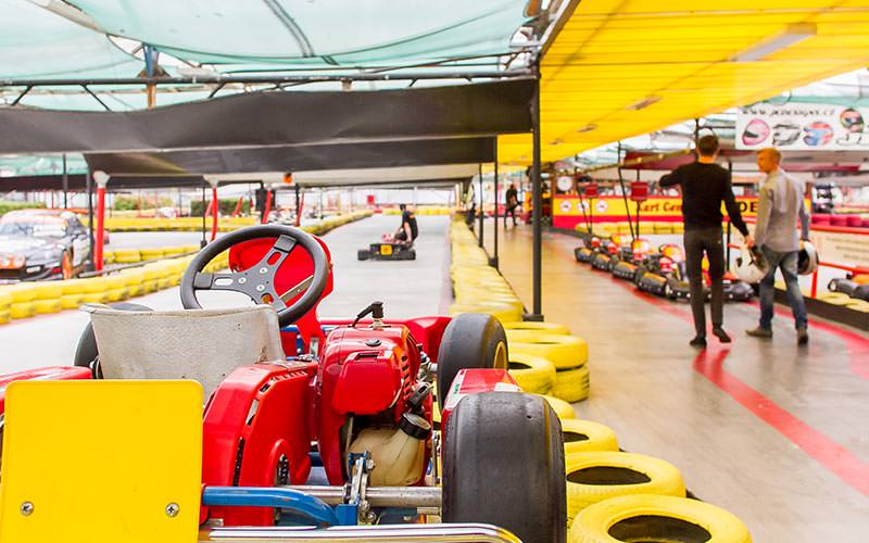 A go kart on an indoor track, with people and the track in the background