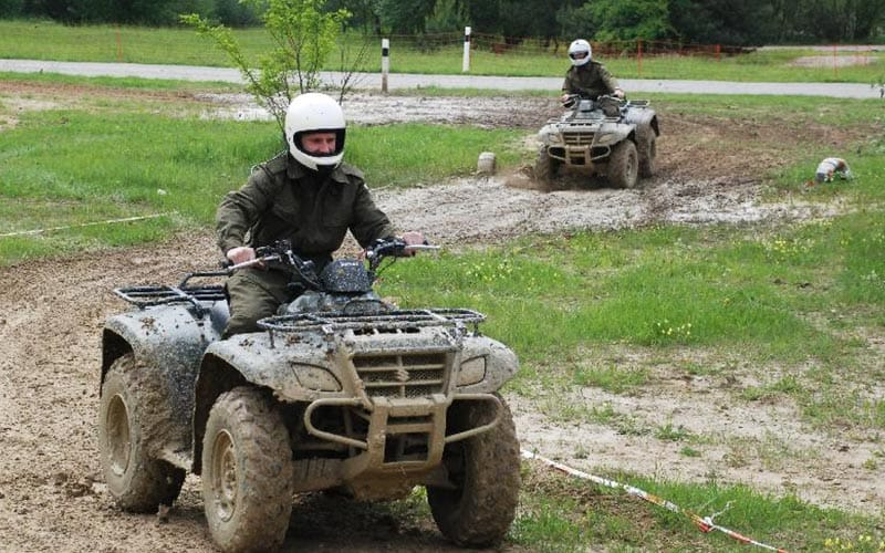 Two quad bikes riding through the mud