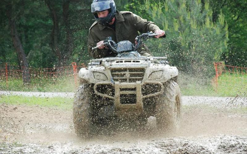 A quad bike driving through a very muddy field