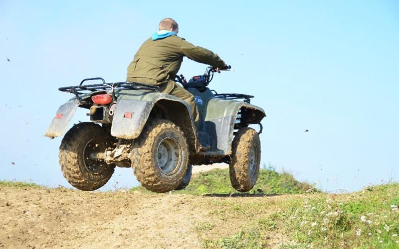A back shot of someone riding a quad bike over a hill on a cloudless day