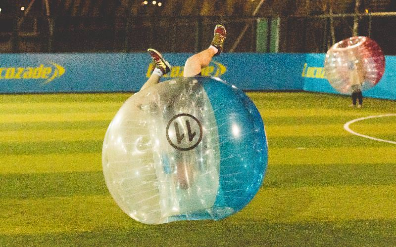 A person flipping upside in a blue inflatable bubble
