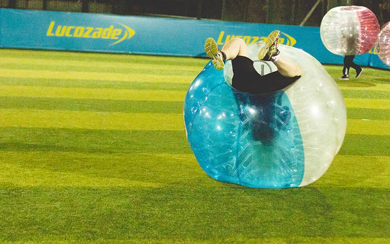 A person flipping over in a blue inflatable bubble on an astroturf pitch