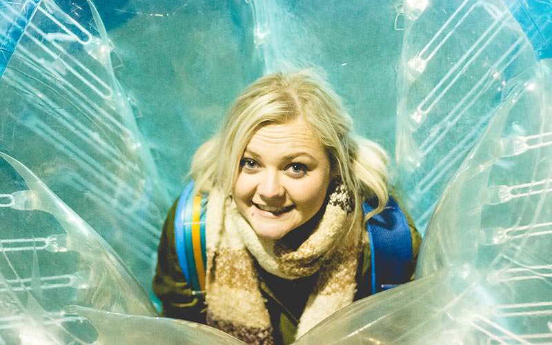 A girl leaning forward and smiling in an inflatable bubble