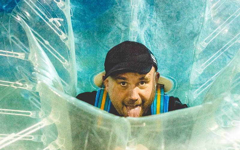 A man leaning forward and sticking his tongue out whilst wearing an inflatable bubble