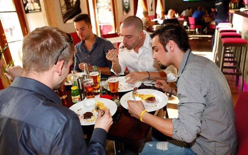 Image of a group of men sitting eating at a table