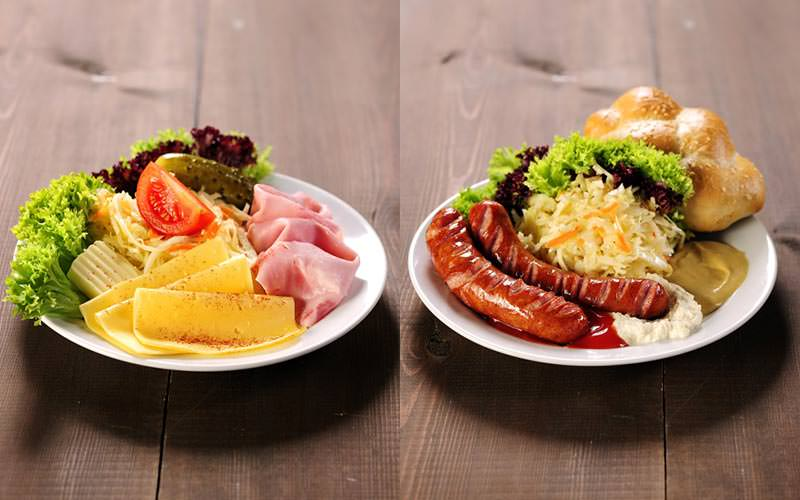 Two plates of food on a table, with meats and salads on