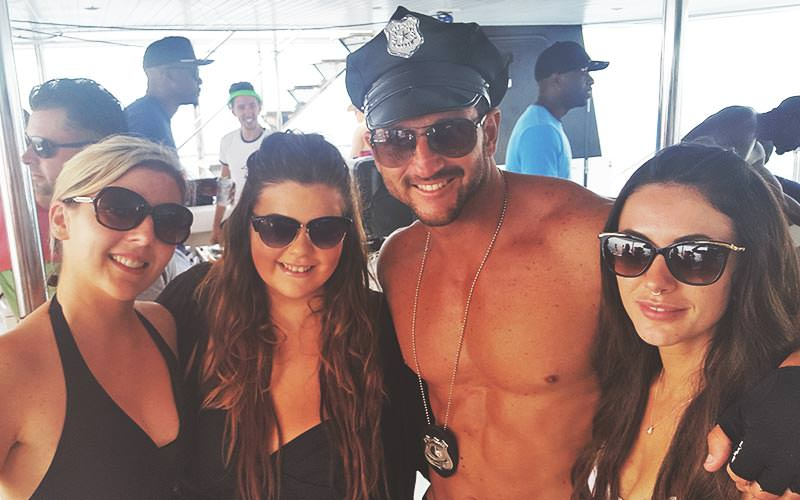 Three women posing with a semi-naked man in a policeman's hat