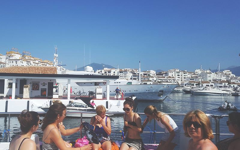People sat on a boat with a marina in the background