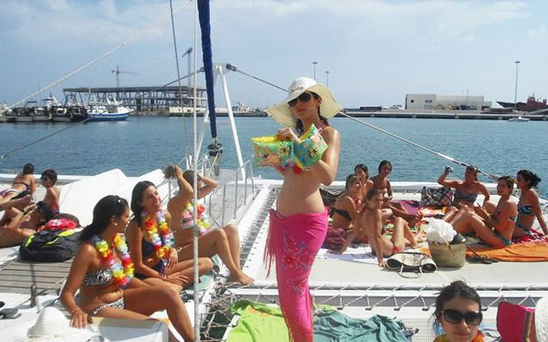 People sat on top of the top deck of a boat, with a woman stood in the middle