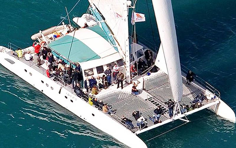 A catamaran full of people, sailing on the sea