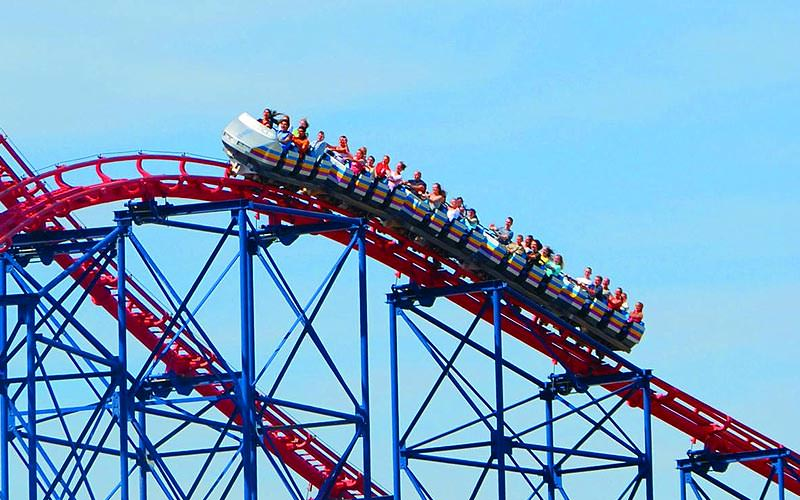 A red and blue rollercoaster full of people, going up a steep incline